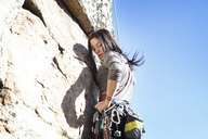 Side view of woman rock climbing against clear sky - CAVF07818