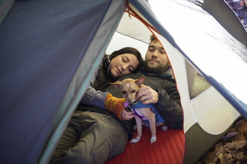 Couple with dog relaxing in tent - CAVF07827