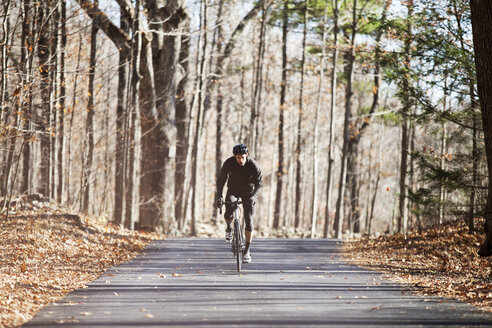 Athlete riding bicycle on road in forest - CAVF07860