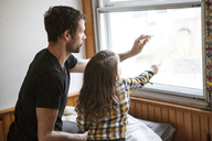 Father and son drawing on window glass while kneeling on bed at home - CAVF07872