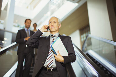 Businessman talking on cell phone going down escalator - CAIF15749