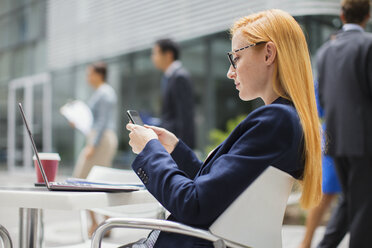 Businesswoman using cell phone at table outside - CAIF15752