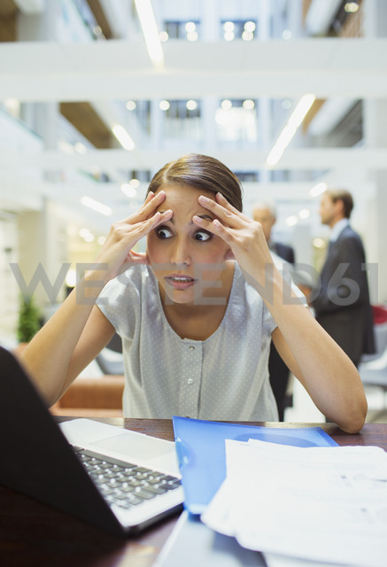 Stressed businesswoman working in office building - CAIF15761