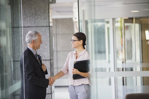 Business people shaking hands in office building - CAIF15767