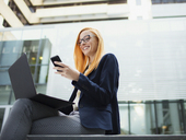 Businesswoman sitting on bench using cell phone - CAIF15773
