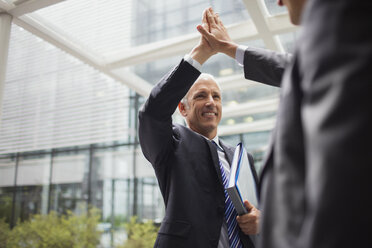 Businessmen high fiving outside of office building - CAIF15776