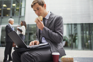 Businessman eating lunch while working outside office building - CAIF15779