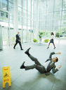 Businessman slipping on floor of office building - CAIF15785