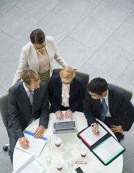 Business people gathered around laptop at table in office building - CAIF15788