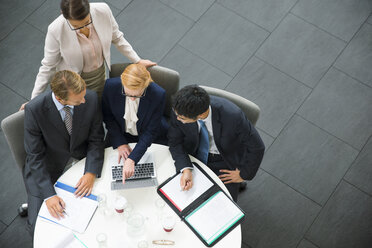 Business people gathered around laptop in office building - CAIF15794