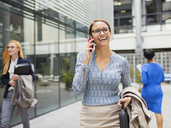 Businesswoman talking on cell phone outside of office building - CAIF15800