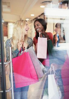 Women carrying shopping bags in store - CAIF15812