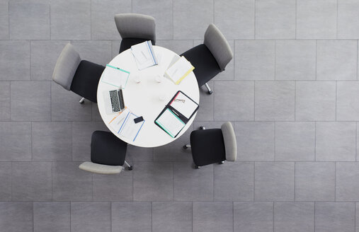 Paperwork scattered on meeting table in office building - CAIF15815