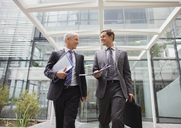 Businessmen walking out of office building together - CAIF15821