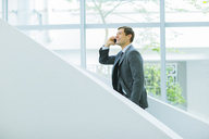 Businessman talking on cell phone on stairs of office building - CAIF15824