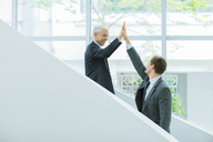Businessmen high fiving on staircase of office building - CAIF15827