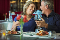 Smiling happy mature couple looking at each other and holding glasses with red wine in restaurant - CAIF15851