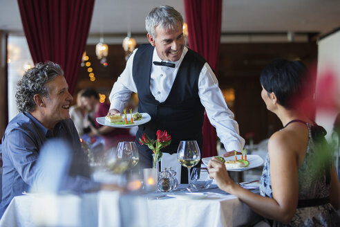 Smiling waiter serving fancy dishes to mature couple sitting at table in restaurant - CAIF15860