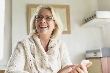 Smiling senior woman in sweater texting with cell phone in kitchen - CAIF15899