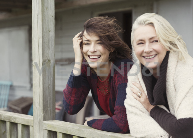 Portrait smiling mother and daughter on windy porch - CAIF15911