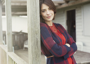 Portrait smiling brunette woman in sweater on porch - CAIF15914
