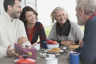 Couples talking and enjoying breakfast at patio table - CAIF15917