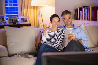 Couple drinking wine and watching TV in living room - CAIF15947