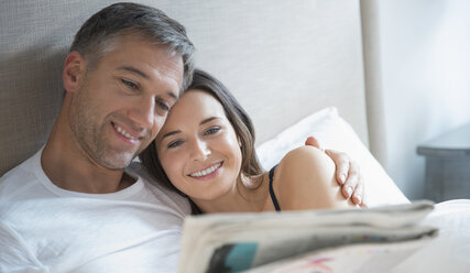 Smiling couple reading newspaper in bed - CAIF15956