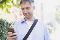 Businessman texting with cell phone outdoors - CAIF15962