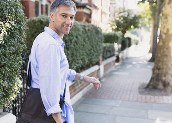 Portrait confident businessman walking and looking back on sidewalk - CAIF15965