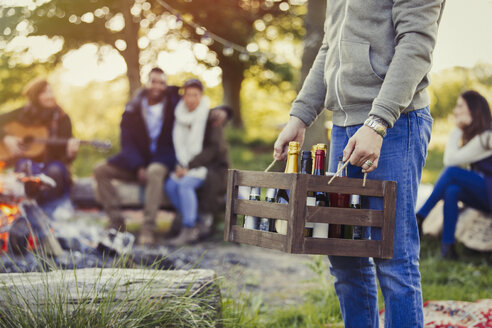 Man carrying crate of wine and beer at campsite with friends - CAIF15989