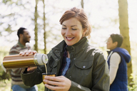 Smiling woman pouring coffee from insulated drink container in woods - CAIF16004