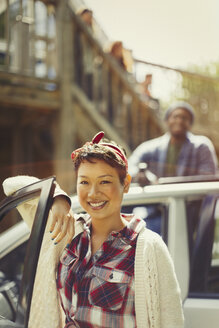 Portrait smiling woman outside car - CAIF16007