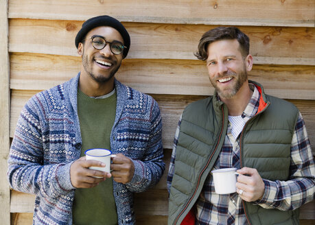 Portrait smiling men drinking coffee outside cabin - CAIF16010
