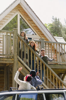 Friends on stairs waving to friends in car outside sunny cabin - CAIF16052