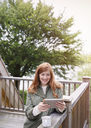 Smiling woman with red hair using digital tablet on cabin balcony - CAIF16055