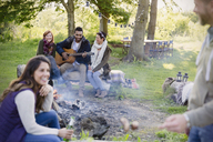 Friends hanging out playing guitar at campfire - CAIF16067