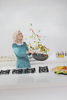 Woman cooking flipping vegetables in skillet in kitchen - CAIF16097