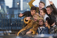 Enthusiastic young adult friends taking selfie at rooftop party - CAIF16118