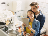 Affectionate young couple using digital tablet in apartment kitchen - CAIF16130