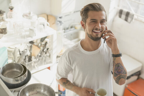 Tattooed young man talking on cell phone and drinking coffee in apartment kitchen - CAIF16142