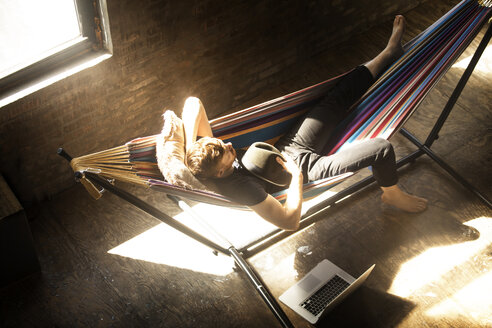 High angle view of man relaxing in hammock tied on stand at home - CAVF07902