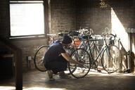 Man repairing bicycle at home - CAVF07911