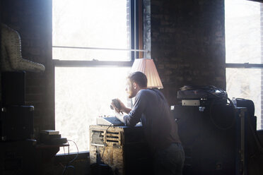 Man with camera standing by window at home - CAVF07923