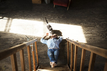 High angle view of man playing with domestic cat while lying on floor at home - CAVF07932