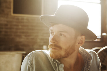 Man wearing hat looking away - CAVF07938
