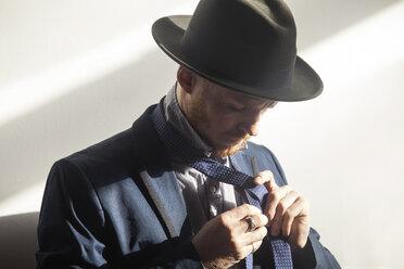 Man tying necktie against wall - CAVF07944