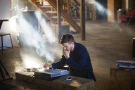 Man concentrating on audio equipment at home - CAVF07950