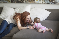Cheerful mother playing with baby girl on sofa at home - CAVF07983