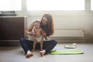Mother holding daughter hands while sitting on floor at home - CAVF07989